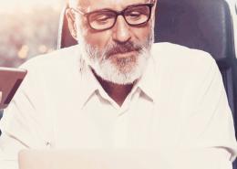 Unternehmenseigentümer mit Brille, grauem Vollbart und weißem Hemd erarbeitet mit seinen Mitarbeitern neue Strategien.