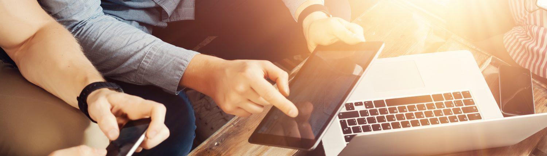 Gruppe von jungen Menschen mit zeigen sich gegenseitig Inhalt auf Smartphones, Tablets und Laptops