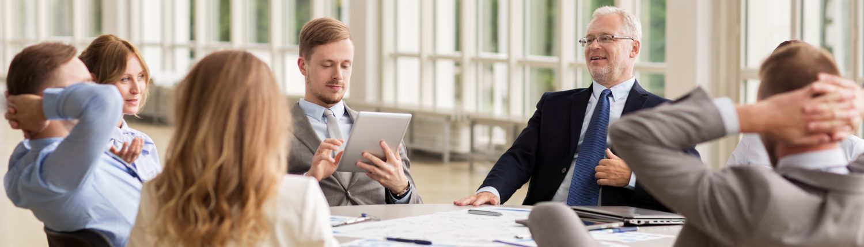 Eine Gruppe von Mitarbeitern sitzt zusammen an einem Tisch und arbeiten.