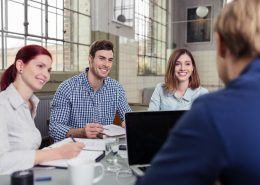 Zufriedene Mitarbeiter arbeiten zusammen an einem gemeinsamen Projekt.