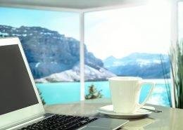 Laptop und Kaffetasse auf einem Tisch vor wunderbarer Aussicht auf See und Berge.