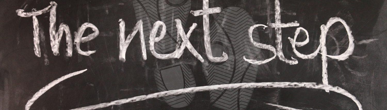 """Schiefertafel mit der Kreide-Aufschrift """"The next Step"""""""