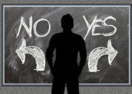 Silhouette von Mann, der vor einer Tafel mit den Aufschriften No und einem Pfeil nach links sowie YES und einem Pfeil nach rechts steht.