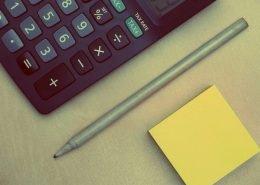 Taschenrechner mit Stift und Post-It