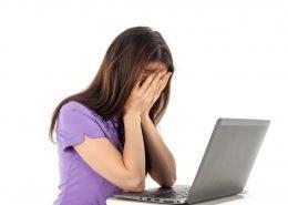 Frau mit Laptop auf einem Tisch schlägt die Hände vor's Gesicht.