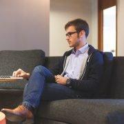 Demotivierter Mitarbeiter mit Jeans, braunen Schuhen und Brille sitzt gelangweilt auf Couch und arbeitet am Laptop