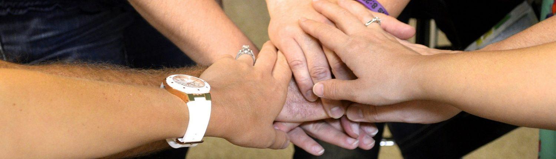 Motivations-Seminar: Gruppe von Menschen im Kreis reichen sich die Hände in der Mitte