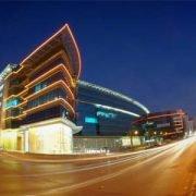 Großes Firmengebäude, zum Teil beleuchtet, bei Nacht.