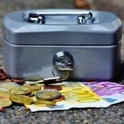 Kleine graue Kasse mit Schlüssel mit Geldscheinen und Münzen im Vordergrund als Symbol für Liquidität.