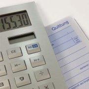 Taschenrechner liegt auf Quittungsblock und symbolisiert wie ausschlaggebend Verbindlichkeiten sind.