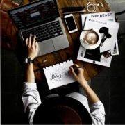 Draufsicht eines Mannes am Arbeitsplatz mit Laptop, Zeitschriften, Cappuccino und Handy.