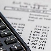 Taschenrechner, der auf einem Blatt Papier mit einer Kalkulation liegt